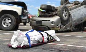 Body bag and car lying on road