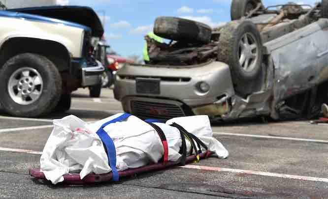Bidy bag and car lying on road